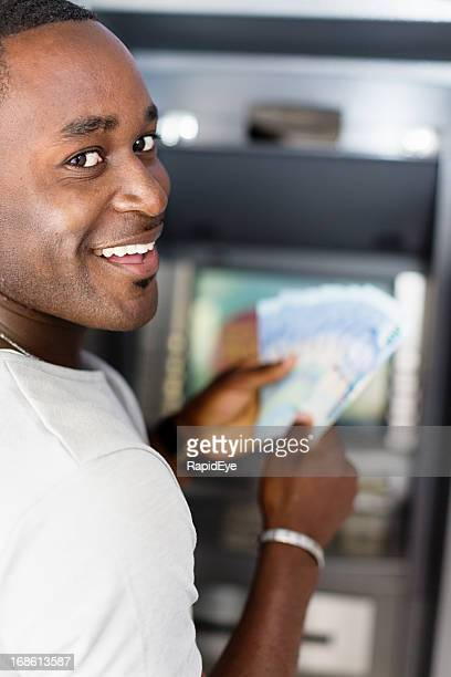 man smiles over shoulder as he gets money from atm - south african currency stock photos and pictures
