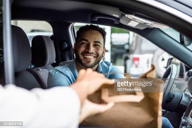 man smiles while picking up curbside order - picking up stock pictures, royalty-free photos & images