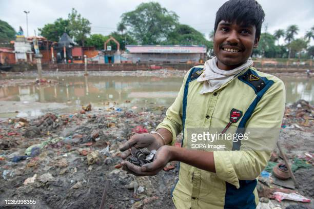 Man smiles while showing off coins smeared in black sand from worship waste in Ganges Canal at Muradnagar. Locals search for valuable items among...