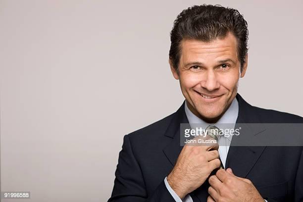 Man smiling, adjusting his tie.