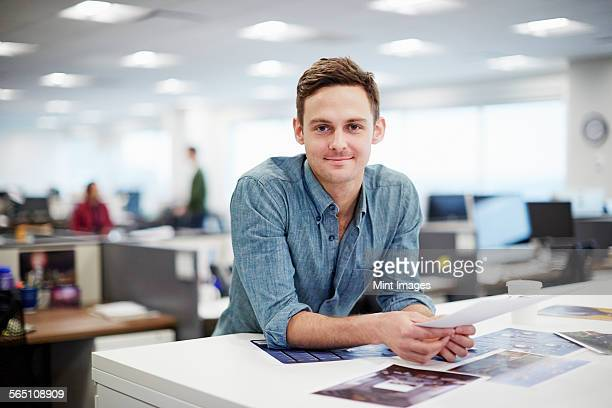 a man smiling and leaning forward on his desk. - differential focus stock pictures, royalty-free photos & images