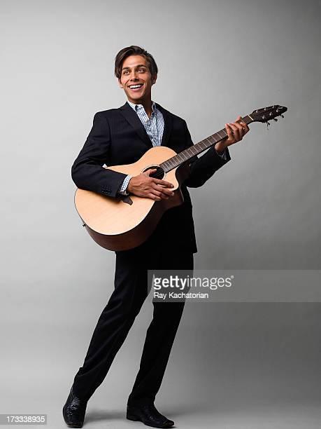 Man smiling and playing guitar