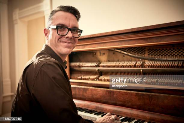 man smiling and playing piano - heshphoto imagens e fotografias de stock