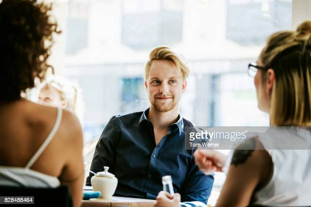 Man Smiling As He Talks With Friends In Cafe