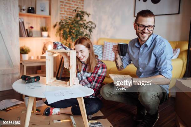 Man smiling at camera while his wife assembling crate