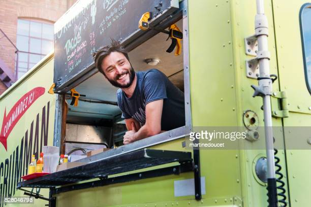 man smiling at clients in food truck in city streets. - food truck stock photos and pictures