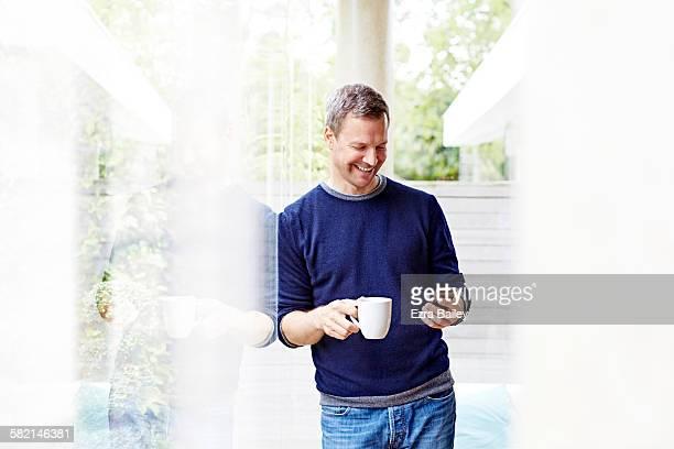 man smiling at phone relaxing with coffee - homem 45 anos imagens e fotografias de stock