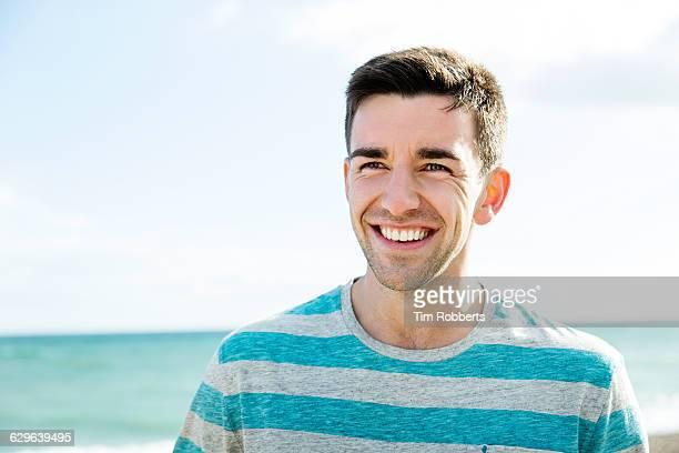 man smiling at seaside. - ボーダーシャツ ストックフォトと画像