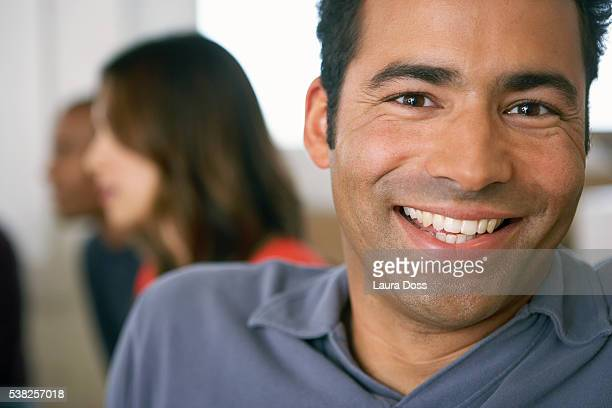 man smiling, co-workers in the background - laura belli foto e immagini stock