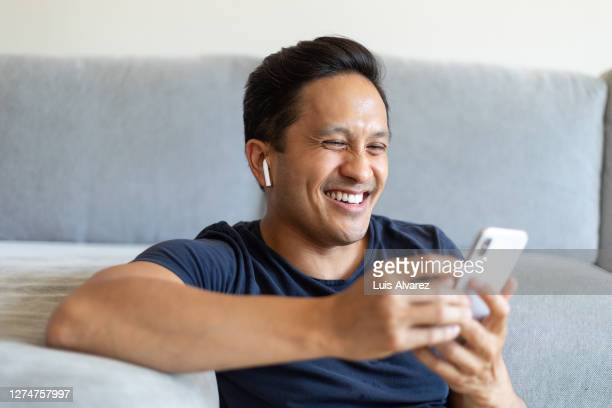man smiling during a video call on his cell phone at home - bluetooth stock pictures, royalty-free photos & images