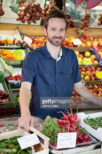 Lächelnder Mann in Produkten stehst