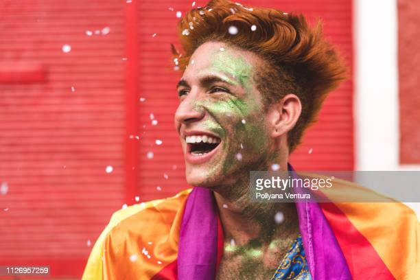 man smiling in the rain of confetti - parade stock pictures, royalty-free photos & images