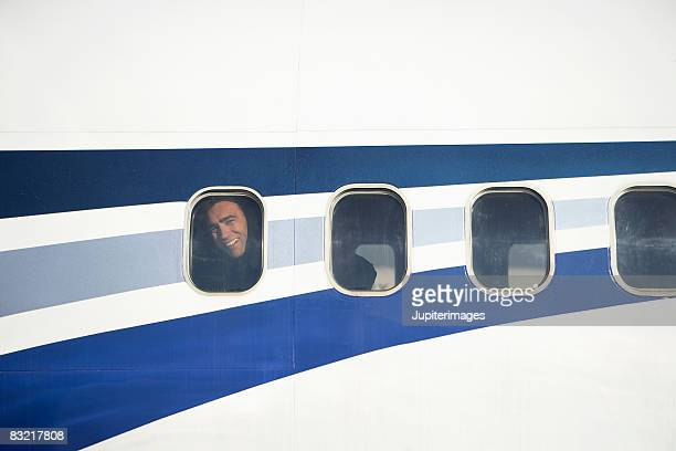 Man smiling inside airplane windows