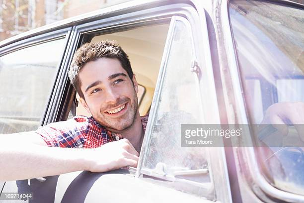 man smiling looking out of car window
