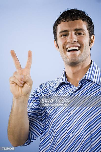 Man smiling peace sign