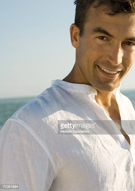 Man smiling, sea in background
