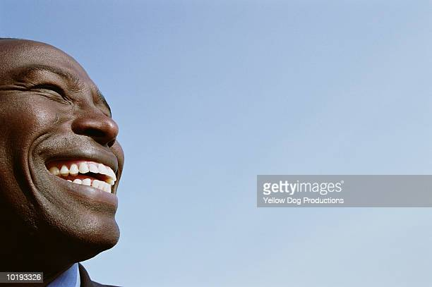 man smiling, side view, close up - stralende lach stockfoto's en -beelden
