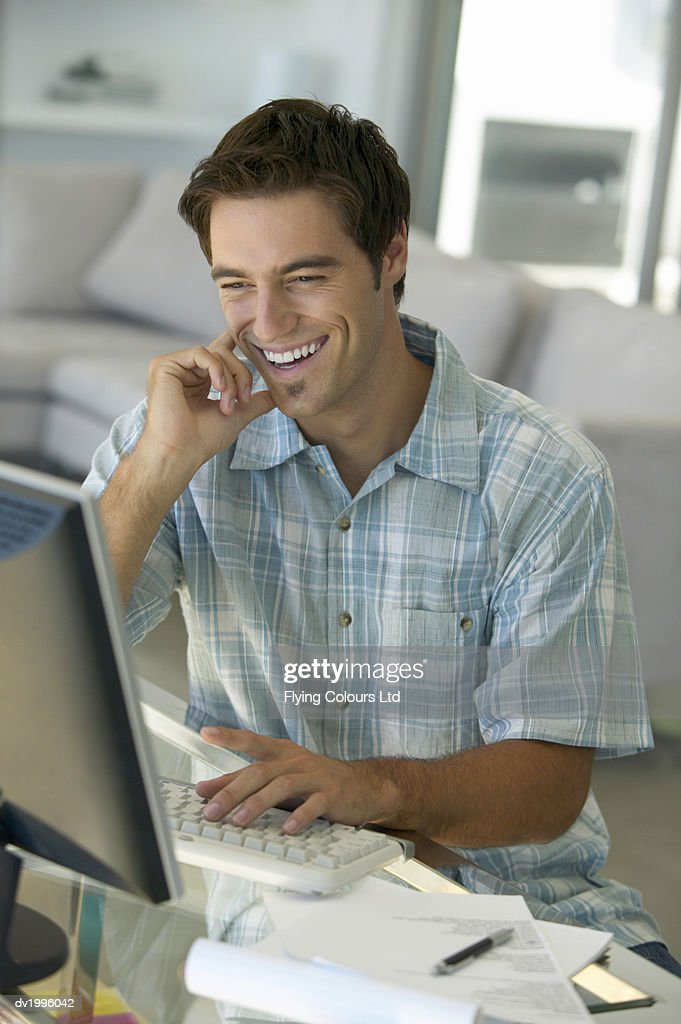 Man Smiling Sitting at a Desk in a Living Room Using a Computer : Stock Photo