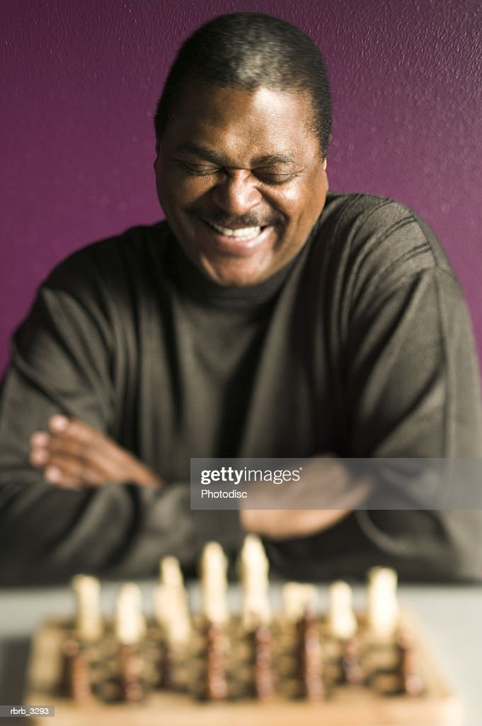 Man smiling sitting in front of a chess board : Foto de stock
