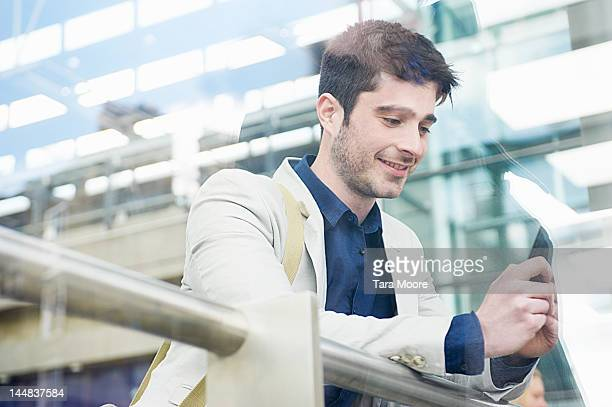 man smiling texting on mobile at station - newtechnology stock pictures, royalty-free photos & images