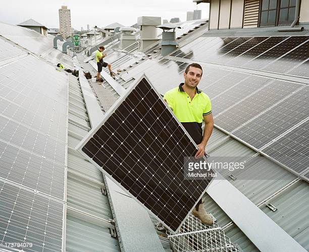 man smiling to camera holding solar panel - solar energy stock pictures, royalty-free photos & images