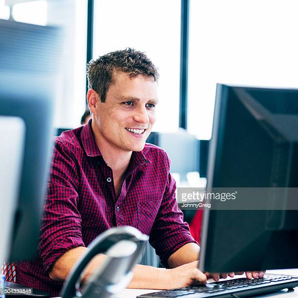 Man smiling using computer in modern office