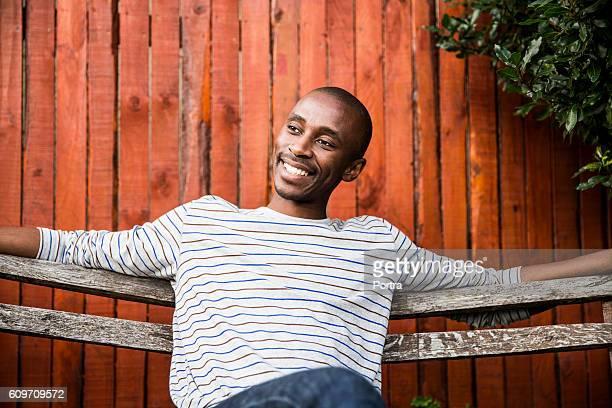 Man smiling while sitting on bench in backyard