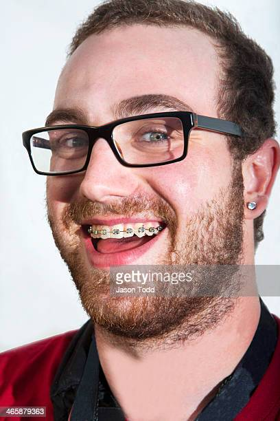 man smiling with braces and glasses on white