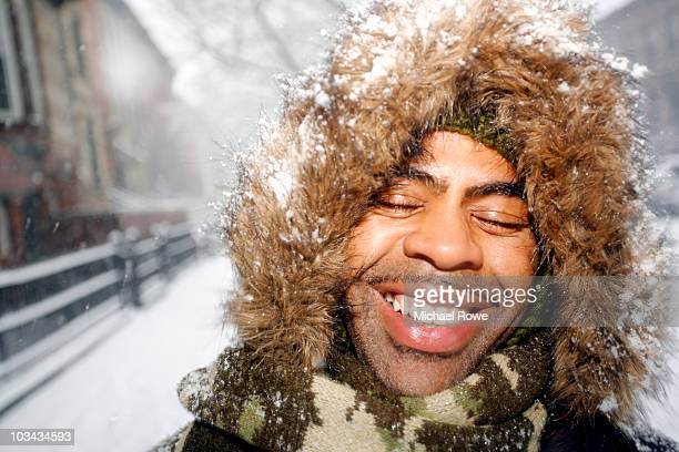 Man smiling with eyes closed covered with snow
