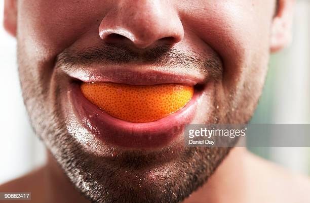 Man smiling with fruit in mouth