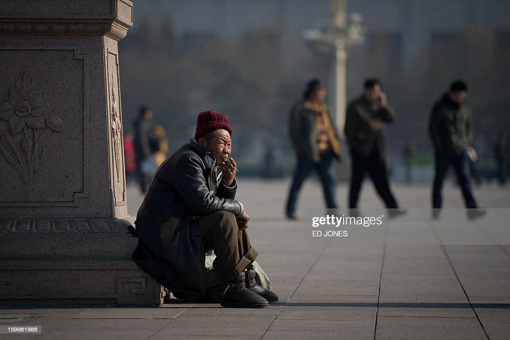 A man smokes a cigarette as he sits in Tiananmen Square in Beijing on January 24, 2013. China's manufacturing activity expanded in January at its fastest pace in two years, HSBC said, the latest sign of recovery in the world's second biggest economy. AFP PHOTO / Ed Jones