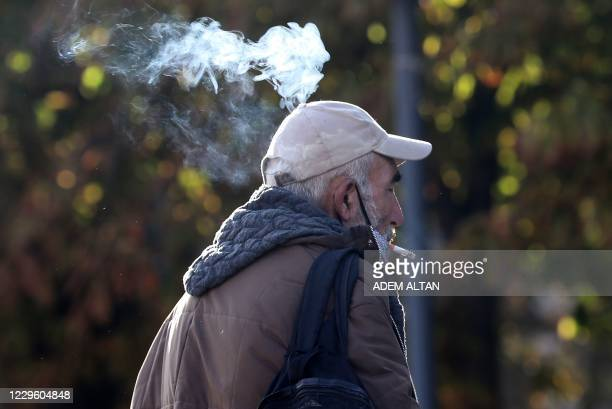 Man smokes a cigarette in a street in Ankara on November 13 after Turkey banned smoking in outdoor public areas as part of restrictions aimed at...
