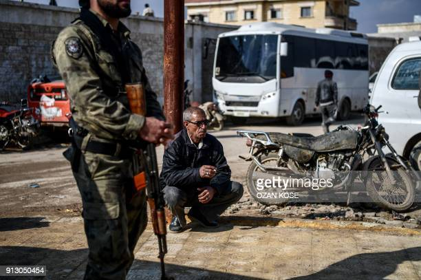 TOPSHOT A man smokes a cigarette next to a Turkishbacked Syrian rebel fighter patrolling in a street during a demonstration in support to Turkish...