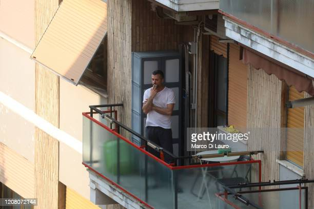 A man smokes a cigarette on his balcony on March 22 2020 in Rome Italy As Italy extends its nationwide lockdown to control the spread of COVID19 its...
