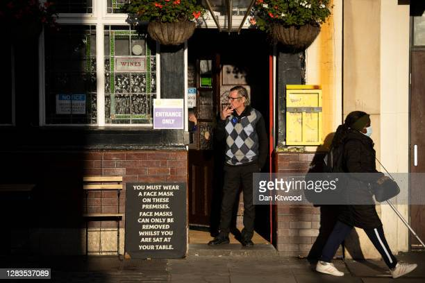 Man smokes a cigarette outside a pub on Kilburn High Street on November 02, 2020 in London, United Kingdom. To curb rising rates of covid-19, the...