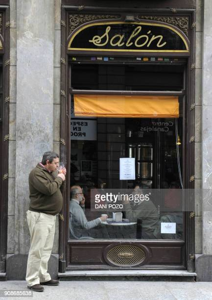 A man smokes a cigarette outside a restaurant in Madrid on January 2 2011 A new Spanish antismoking law takes effect on January 2 prohibiting smoking...