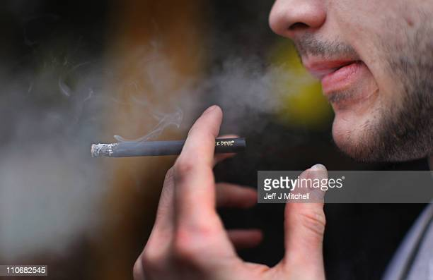 A man smokes a cigarette outside James Harvie Tobacconist on March 23 in Paisley Scotland The Chancellor is expected to implement further measures to...