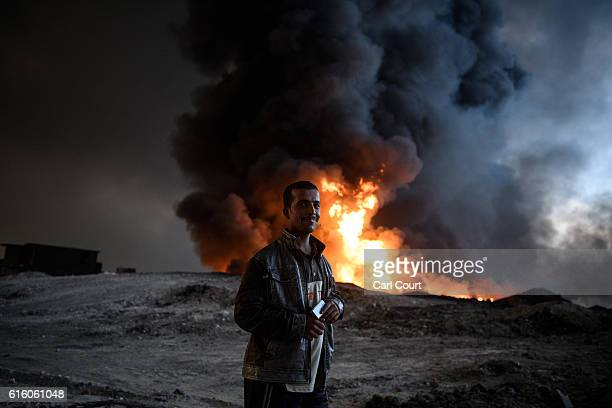 A man smokes a cigarette stand next to an oil field that was set on fire by retreating ISIS fighters ahead of the Mosul offensive on October 21 2016...