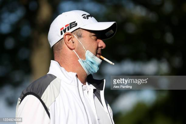 Man smokes a cigarette whilst wearing a face mask before his round of golf at West Essex Golf Course on May 13, 2020 in London, England. The prime...