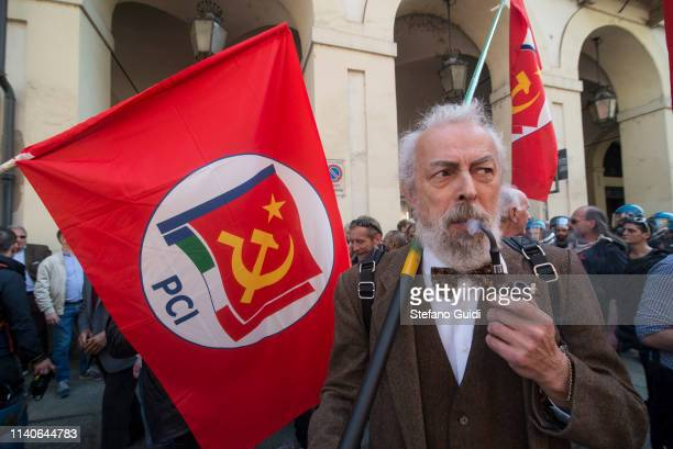 A man smokes a pipe near a communist flag during the march of the May Day procession The Workers' Day or May Day is celebrated on 1 May each year in...