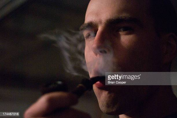 Man smokes a pipe, with smoke visible against a dark background.
