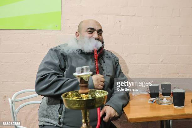 A man smokes a shisha during a street festival in the southwestern suburb of Lakemba on May 27 2017 in Sydney Australia Muslims around the world mark...