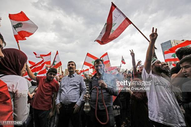 A man smokes a waterpipe as others wave Lebanese national flags during a demonstration in the northern city of Tripoli's alNour Square on October 23...