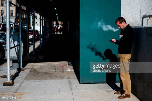 A man smokes an electronic cigarette also known as an ecigarette in New York on November 15 2017  PHOTO / Jewel SAMAD