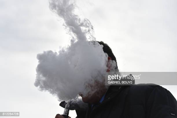 A man smokes an electronic cigarette in the street on February 24 2016 in Milan AFP PHOTO / GABRIEL BOUYS / AFP / GABRIEL BOUYS