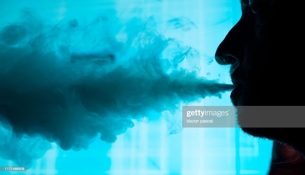Man smokes an electronic cigarette in town . : Stock Photo