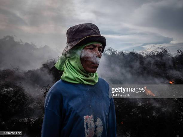 A man smokes as they burn plastic waste at a import plastic waste dump in Mojokerto on December 4 2018 in Mojokerto East Java Indonesia Indonesia's...