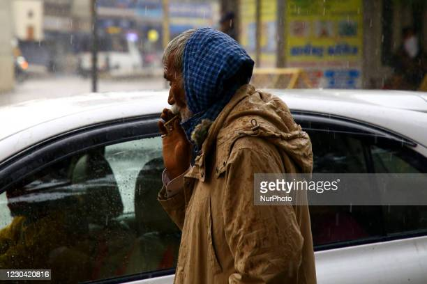 Man Smokes 'Bidi' a Small Hand Rolled Cigarette During Rain in Ajmer, the Indian State of Rajasthan on 04 January 2021.