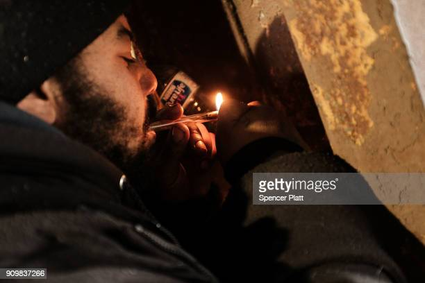 A man smokes crack under a bridge where he lives with other addicts in the Kensington section of Philadelphia which has become a hub for heroin use...