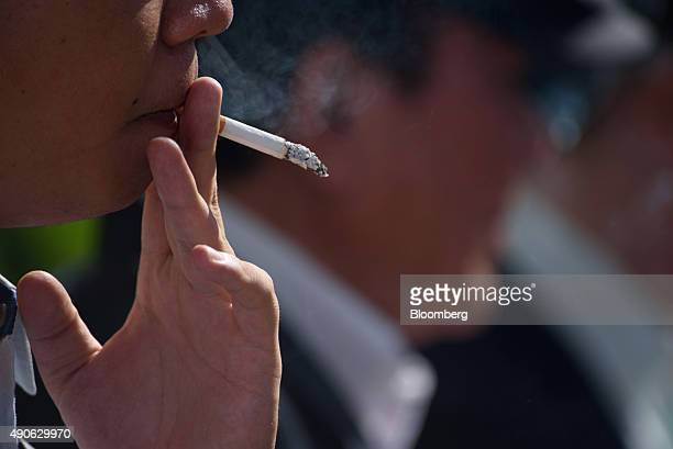 A man smokes in a designated smoking area in Tokyo Japan on Wednesday Sept 30 2015 Japan Tobacco Inc fell to the lowest in six months after agreeing...